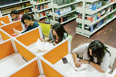 Four students are reading in a library